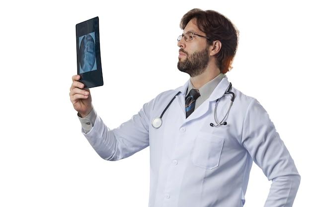 Männlicher arzt, der eine röntgenaufnahme auf einer weißen wand betrachtet