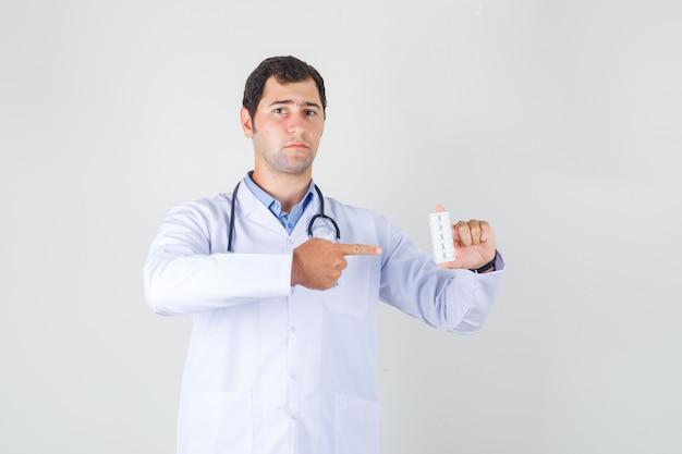 Männlicher arzt, der finger auf pillen im weißen kittel zeigt und ernst schaut. vorderansicht.