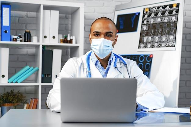 Männlicher arzt der gemischten rasse, der an seinem arbeitstisch im krankenhaus sitzt