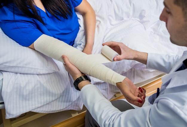 Männlicher arzt, der hand von weiblichen patienten verbindet.