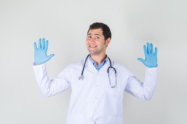 Männlicher arzt, der höflich ablehnungsgeste im weißen kittel, in den handschuhen zeigt und fröhlich aussieht