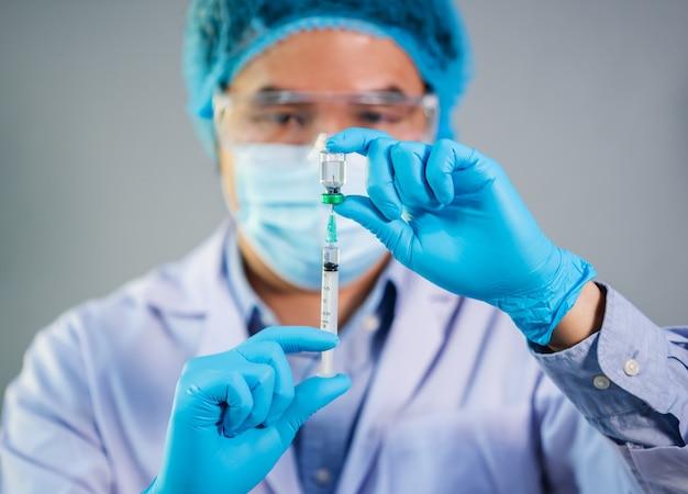 Männlicher arzt, der impfstoffflasche in spritzeninjektionsmedizin zieht