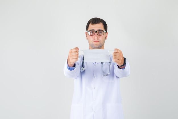 Männlicher arzt, der medizinische maske im weißen kittel, in der brille hält und vorsichtig schaut. vorderansicht.