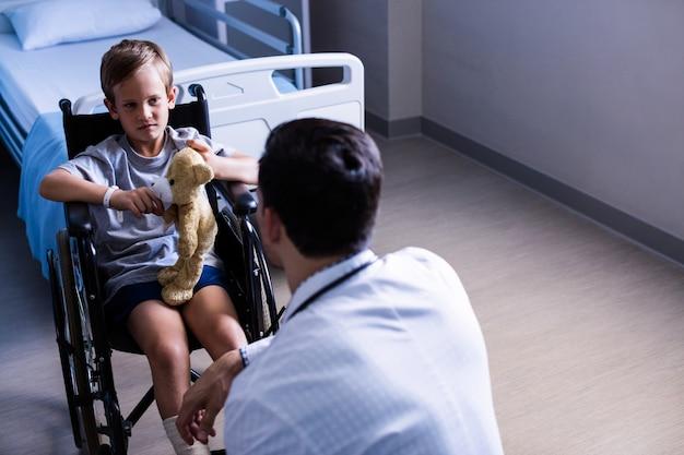 Männlicher arzt, der mit dem kinderpatienten in der station interagiert