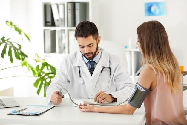 Männlicher arzt, der mit weiblichem patienten in klinik arbeitet