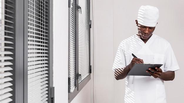Männlicher arzt, der neben den krankenhausfenstern steht