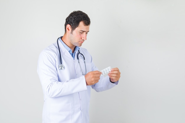 Männlicher arzt, der packung der pillen im weißen kittel hält und ernst schaut