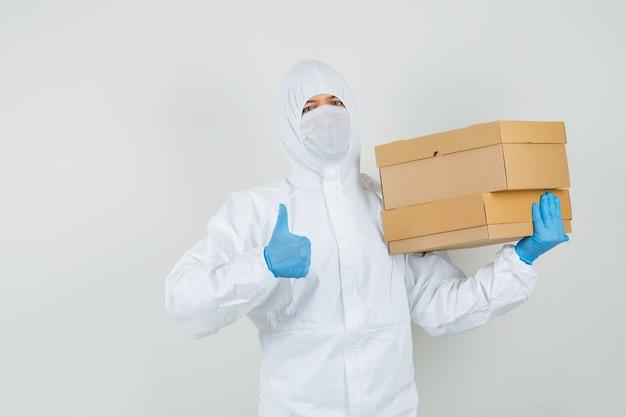 Männlicher arzt, der pappkartons hält und daumen oben im schutzanzug zeigt