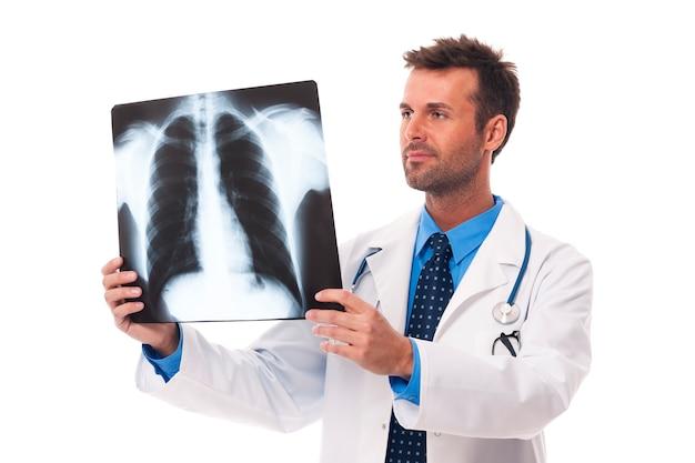 Männlicher arzt, der röntgenbild untersucht