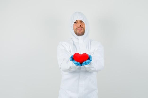 Männlicher arzt, der rotes herz im schutzanzug hält