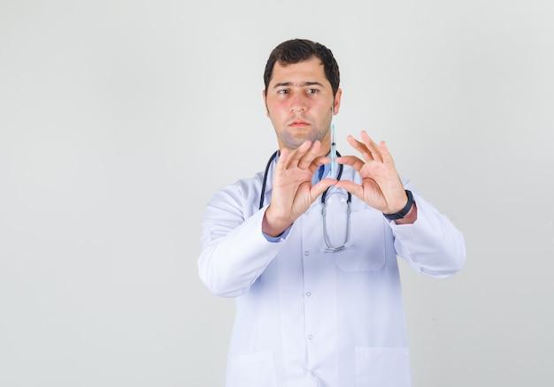 Männlicher arzt, der spritze zur injektion in der vorderansicht des weißen mantels hält.