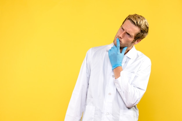 Männlicher arzt der vorderansicht, der auf gelbem hintergrund menschliches medizin-covid-gefühl denkt