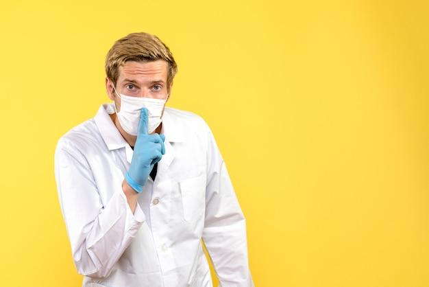 Männlicher arzt der vorderansicht, der bittet, auf pandemie-covid-gesundheitsmediziner mit gelbem hintergrund ruhig zu sein