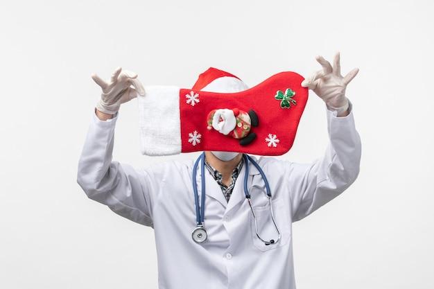 Männlicher arzt der vorderansicht, der feiertagssocke auf weißem wand-weihnachts-gesundheitsvirus hält