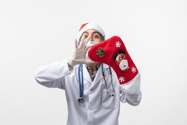 Männlicher arzt der vorderansicht, der große rote socke an feiertagen des weißen wandvirus hält