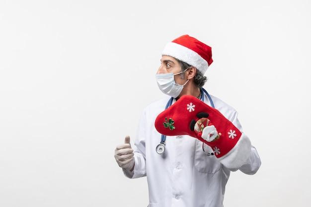 Männlicher arzt der vorderansicht, der große rote socke auf weißwandvirus-covid-feiertag hält