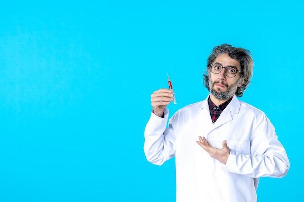 Männlicher arzt der vorderansicht, der injektion auf blau hält