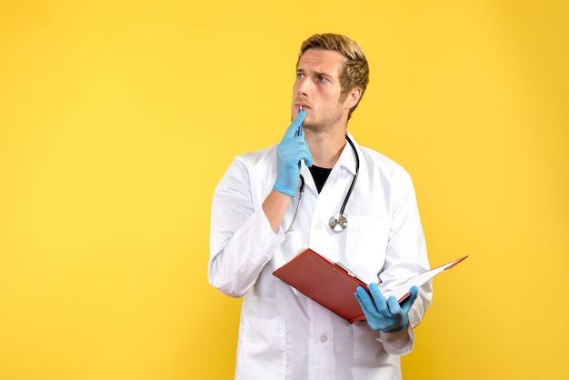 Männlicher arzt der vorderansicht, der notizen auf menschlichem virus des gelben hintergrundgesundheitsarztes schreibt