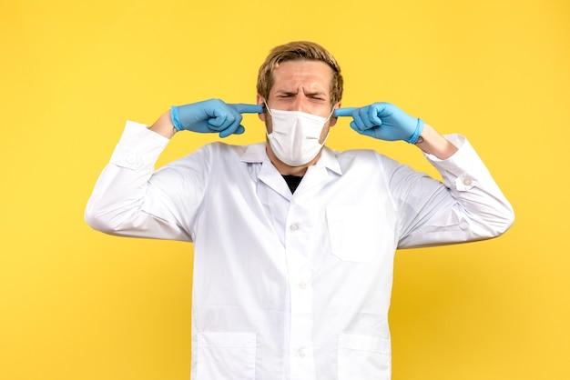 Männlicher arzt der vorderansicht, der seine ohren auf pandemie-covid-gesundheitsmediziner mit gelbem hintergrund steckt