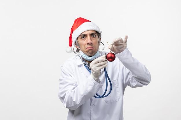 Männlicher arzt der vorderansicht, der spielzeug auf neujahrsgesundheit des weißen wandvirus beobachtet