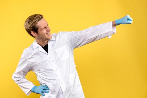 Männlicher arzt der vorderansicht freut sich über gelben hintergrund covid-human hospital medic