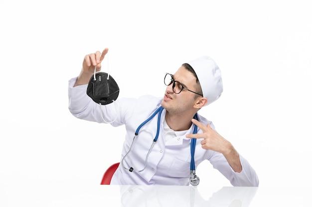 Männlicher arzt der vorderansicht im medizinischen anzug, der spezielle schwarze maske hält