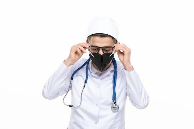 Männlicher arzt der vorderansicht im medizinischen anzug, der spezielle schwarze maske trägt