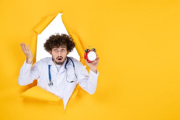 Männlicher arzt der vorderansicht im medizinischen anzug, der uhren auf einem gelben gesundheitsfarbkrankenhaus hält, das medizinzeitmedizin einkauft