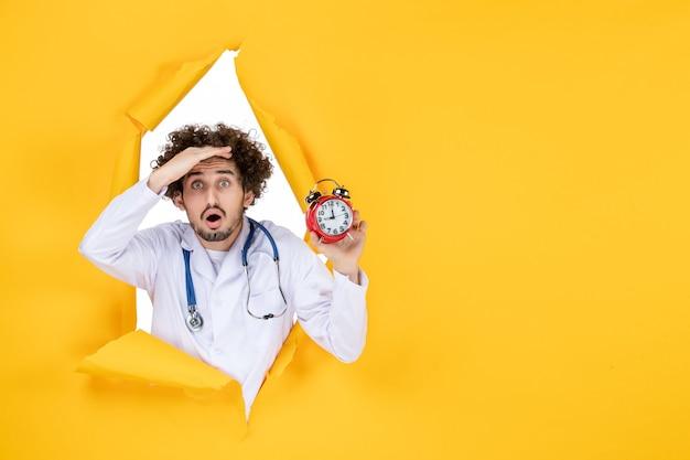 Männlicher arzt der vorderansicht im medizinischen anzug, der uhren auf gelber farbe krankenhausmediziner-einkaufsmedizinzeit hält
