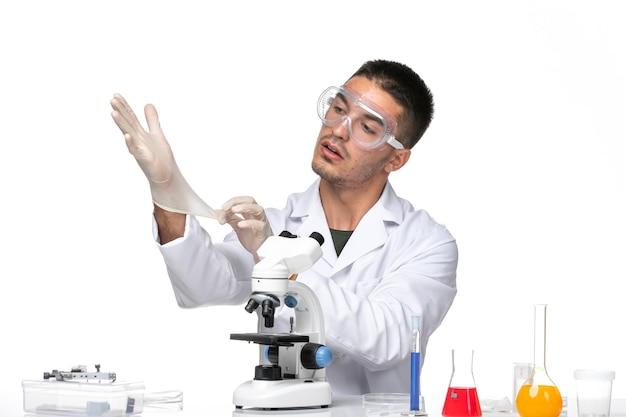 Männlicher arzt der vorderansicht im weißen medizinischen anzug, der handschuhe auf weißem raum trägt