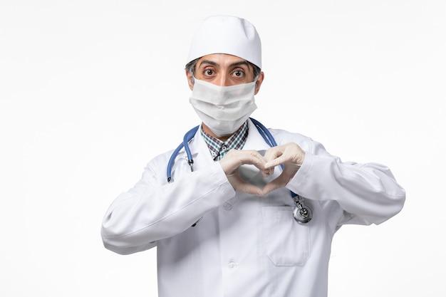 Männlicher arzt der vorderansicht im weißen medizinischen anzug, der maske wegen covid zeigt, das herzzeichen auf weißem schreibtisch zeigt