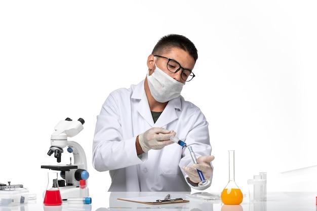 Männlicher arzt der vorderansicht im weißen medizinischen anzug mit maske wegen der koviden arbeit am weißen raum