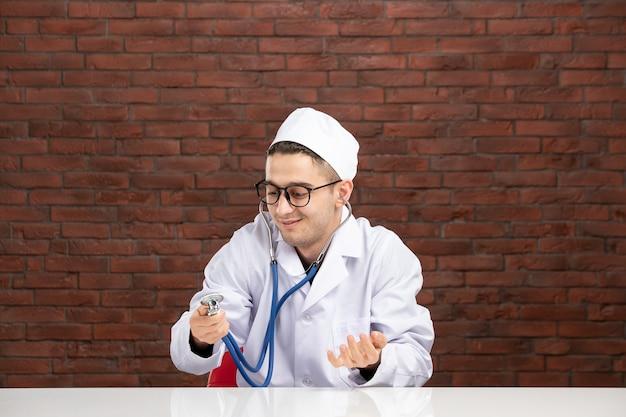 Männlicher arzt der vorderansicht im weißen medizinischen anzug mit stethoskop