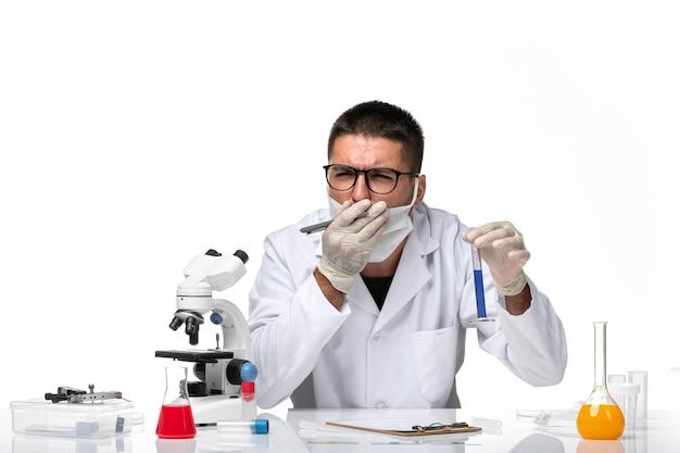 Männlicher arzt der vorderansicht im weißen medizinischen anzug und mit der maske, die mit lösung auf weißem raum arbeitet
