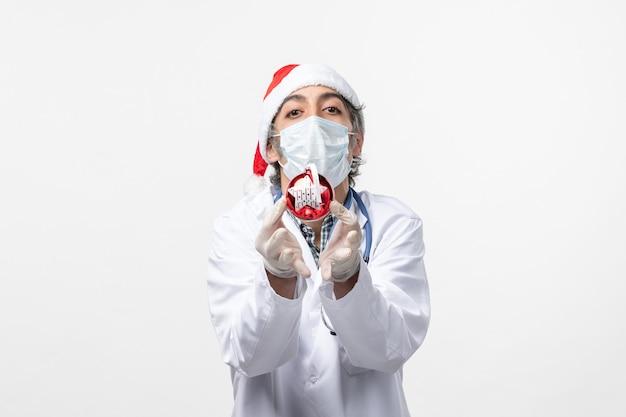 Männlicher arzt der vorderansicht in der maske mit spielzeug auf weißem schreibtischgesundheits-neujahrsvirus