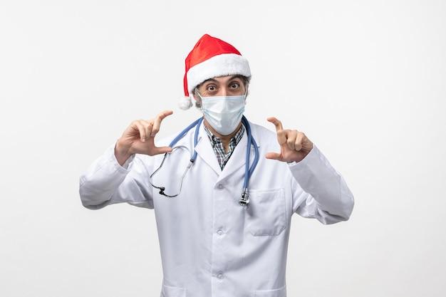 Männlicher arzt der vorderansicht mit maske auf einem weißen wandpandemie-covid-feiertagsvirus