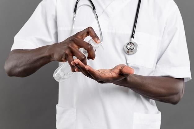 Männlicher arzt, der zu seiner sicherheit händedesinfektionsmittel verwendet