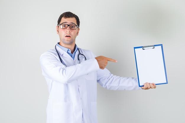 Männlicher arzt im weißen kittel, brille, die finger auf zwischenablage zeigt