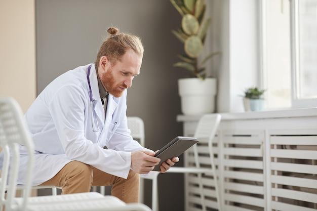 Männlicher arzt im weißen kittel, der etwas auf digitalem tablett beobachtet, das auf stuhl am korridor des krankenhauses sitzt