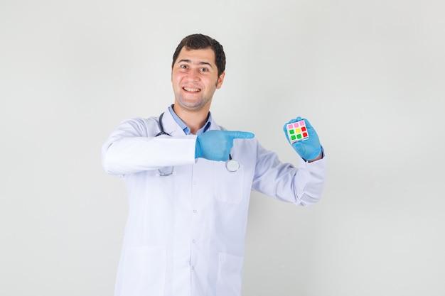 Männlicher arzt im weißen kittel, handschuhe zeigen mit dem finger auf rubiks würfel und sehen fröhlich aus