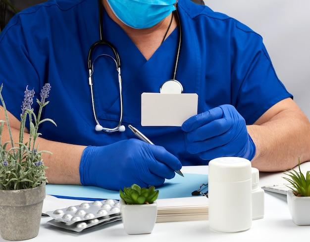 Männlicher arzt in blauer uniform sitzt an einem weißen tisch und schreibt mit sterilen handschuhen an den händen in ein notizbuch