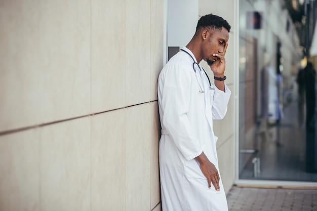 Männlicher arzt in der klinik, der seinen kopf hält, hat gesundheitliche probleme und ist nach einem harten tag müde, depressiv hat nicht das gewünschte ergebnis erzielt, afroamerikanischer arzt ist traurig