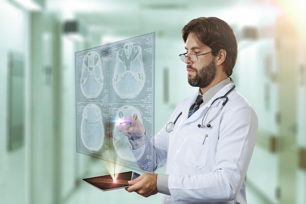 Männlicher arzt in einem krankenhaus, der einen virtuellen bildschirm betrachtet, der aus einer tablette herauskommt