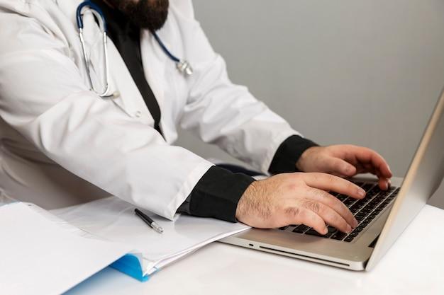 Männlicher arzt in einem weißen kittel arbeitet in einem computer und macht sich notizen. nahansicht.