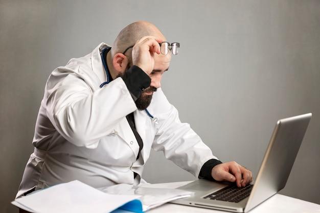 Männlicher arzt in einem weißen kittel schaut überrascht auf den computer und trägt eine brille.