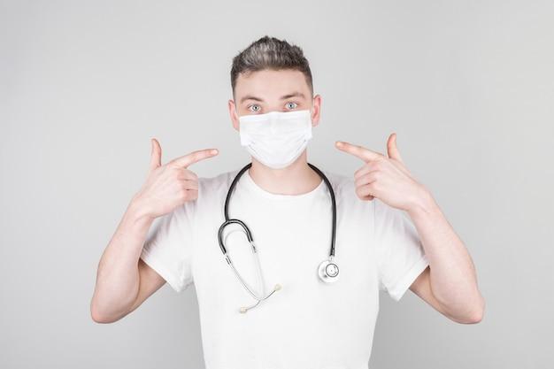 Männlicher arzt in medizinischer uniform zeigt mit den fingern auf eine medizinische maske auf seinem gesicht