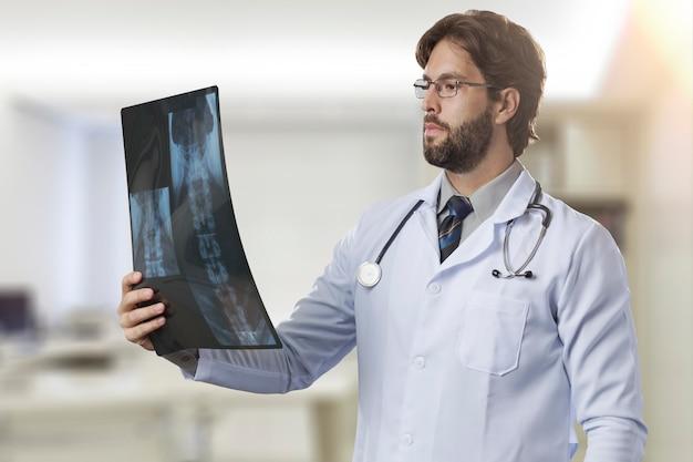 Männlicher arzt in seinem büro, der eine röntgenaufnahme betrachtet