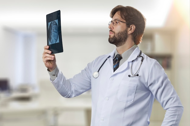 Männlicher arzt in seinem büro, der eine röntgenaufnahme betrachtet.