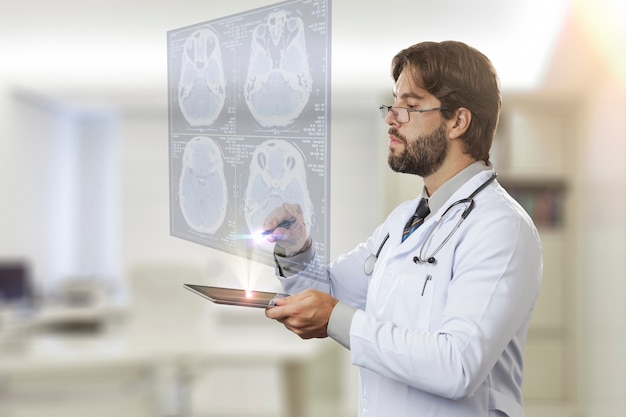Männlicher arzt in seinem büro, der einen virtuellen bildschirm betrachtet, der von einem tablett kommt