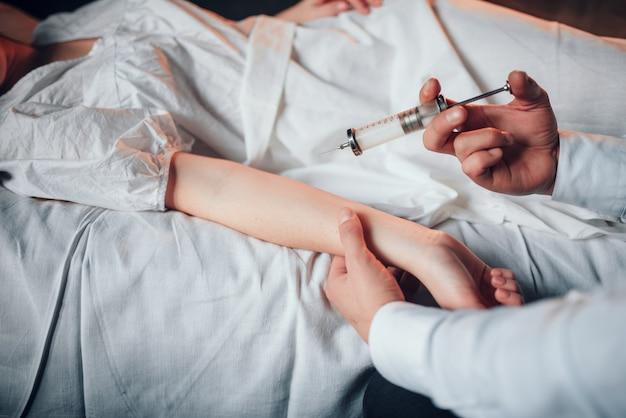 Männlicher arzt macht spritzeninjektion zur kranken frau